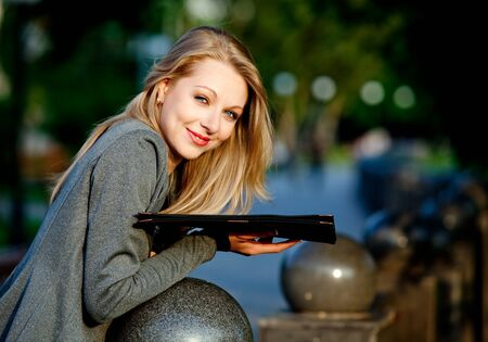Young blond happy businesswoman standing with documents in park