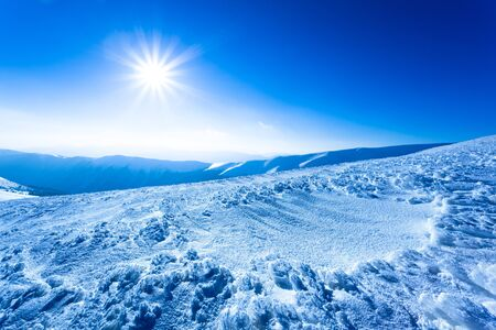 Landscape of snow winter valley and mountains and sun in above on clear winter frosty day. View of winter wonderland nature concept