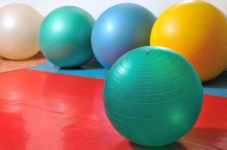 Close photo of sports equipment, fitness balls and sports items in different colors are located nearby