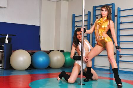 Dance training of two girls on a pole