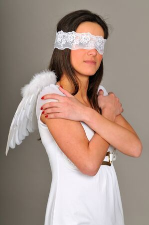 Portrait of young girl with in white dress with angel wings, hands folded, blindfold. Isolated on gray background