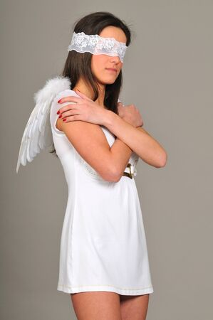 Portrait of young girl with in white dress with angel wings, hands folded, blindfold. Isolated on gray background Stockfoto