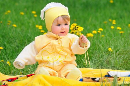 Cute baby in yellow baby clothes is sitting in grassy field with dandelions. Photo portrait outdoors Zdjęcie Seryjne