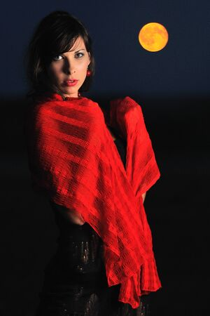 Girl posing looking at camera with red scarf on shoulders, dark time of day, bright moon on background