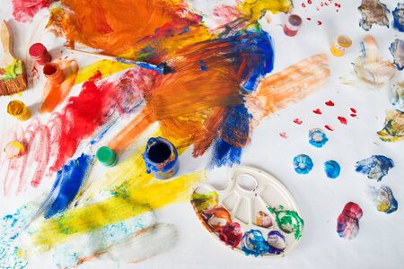 Bright multi-colored childrens drawings with paints, brushes and palette stained with paint
