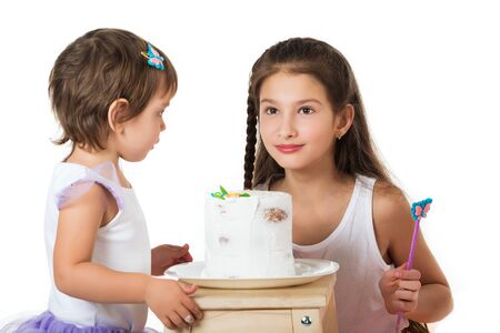 Two little girls near the cake on white