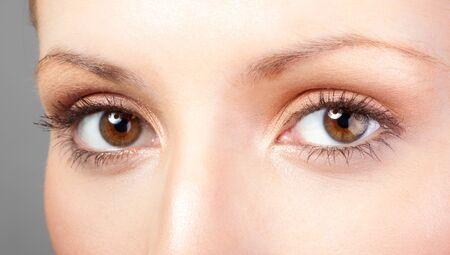 Close-up blauw oog met natuurlijke make-up kijkend naar de zijkant, macro-opname met perfecte huid Stockfoto