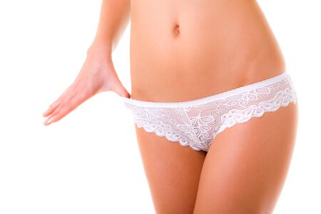 White lace panties on slim womans body over white background in photo studio. Beauty of woman body, womans health concept