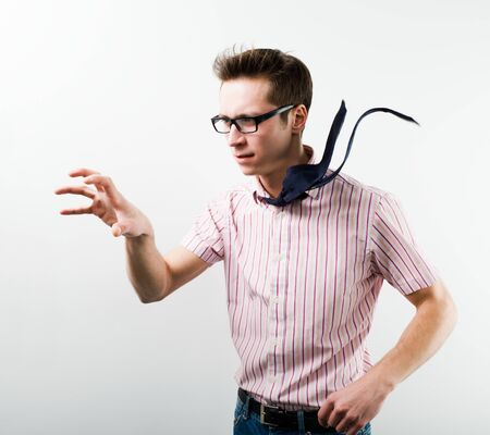 Young man in business casual clothing in glasses standing over white background in photo studio and having idea ponting with hand. Smart casual style and business situations concept