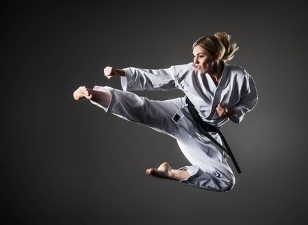 Composite image of karate girl in white kimono with black belt in jump. Purple background and clouds of smoke