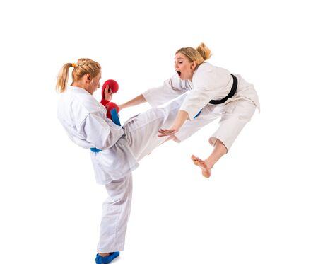 Karate de chicas rubias lindas se dedican a la formación en un kimono sobre un fondo blanco. Joven pareja de atletas preparándose para una actuación. Copyspace