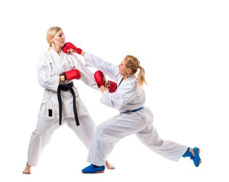 Entrenamiento de boxeo de dos mujeres jóvenes con kimonos blancos y guantes de boxeo. Aislado sobre fondo blanco Foto de archivo