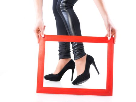 Girl in leather leggings and black high heel shoes holds red wooden frame near her legs
