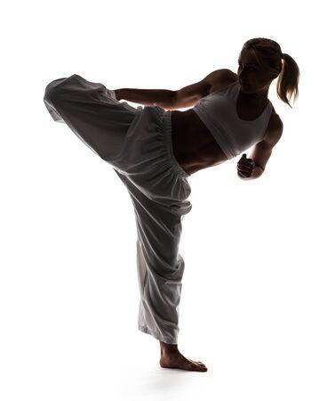 Mujer de karate vestida con kimono y posa mientras está de pie sobre una pierna. Foto de cuerpo entero sobre fondo blanco. Foto de archivo