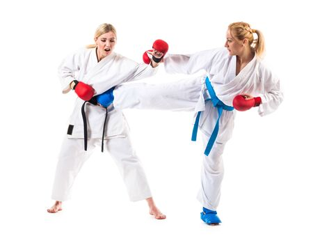Cute blonde girls karate are engaged in training in a kimono on a white background. Young couple of athletes getting ready for a performance. Copyspace