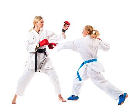 Entrenamiento de boxeo de dos mujeres jóvenes con kimonos blancos y guantes de boxeo. Aislado sobre fondo blanco