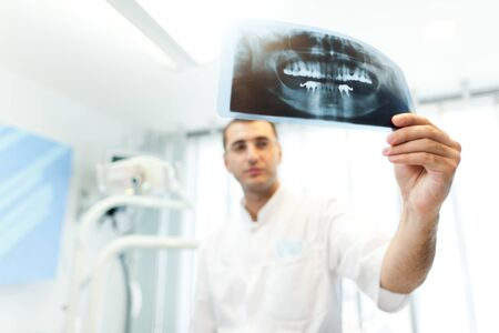 Young doctor dentist man in white uniform standing and looking at tooth picture in dental office in clinic