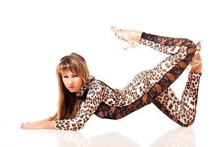Junge, schlanke, schöne Frau mit langen Haaren im Leopardenkostüm, die in Katzenpose auf weißem Hintergrund sitzt. Schönheit des Körper- und Tanzkonzepts der Frau Standard-Bild