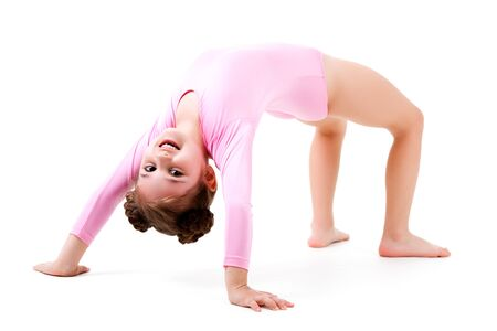 Small positive girl in pink gymnastic jumpsuit standing in bridge pose and smiling over white background. Active healthy lifestyle, hobbies and sporty children concept