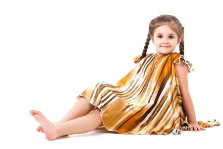 Small girl with long hair in golden striped dress with wide hem over grey background. Trendy children wear, fashion and beauty concept
