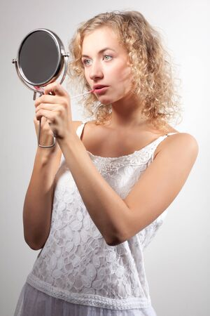 Young slim beautiful blond woman with curly hair in white sexy mini dress looking at small mirror and smiling over white background. Beauty of womans body and stylish summer clothing concept