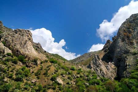 Slope of rocky cliff of unusual shape in the Crimean mountains. Blue cloudless sky in background Banco de Imagens