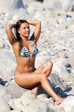 Woman with closed eyes, arms raised up and near head, in swimsuit sitting on stones on seashore