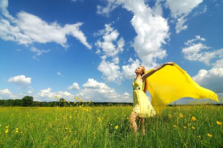 A girl in a yellow dress poses with hands up in a green field with a silk cloth in her hands. Beautiful outdoor photo Stockfoto