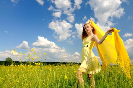 Beautiful woman in a yellow cocktail dress posing in a green field with airiness silk in her hands Stock fotó - 138473574