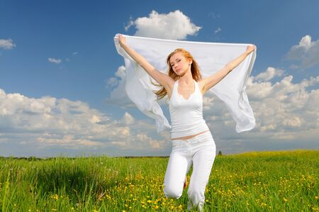 Woman in white clothes posing in a flower field with silk cloth in her hands, arms raised up. Blue sky on background Stock fotó - 138473534