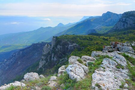 View of the huge rocky cliffs and green valley covered with forest. Beautiful mountain landscape Banco de Imagens