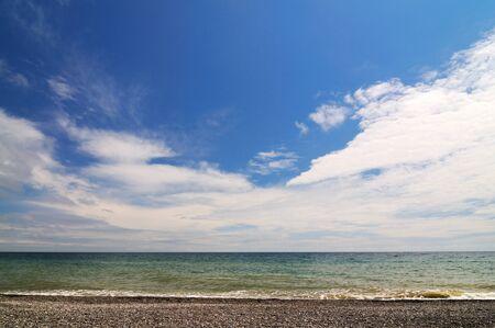 Sea shore and rocky beach, blue cloudy sky Zdjęcie Seryjne