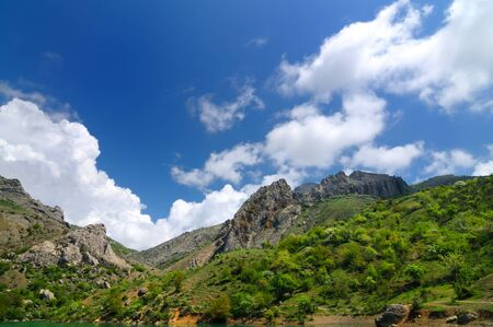 Beautiful landscape in Crimea, slope of mountain covered with green grass, rocks and stones