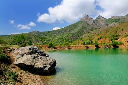Mountain lake with bright green water, large stone in foreground on shore. Green trees and plants in background