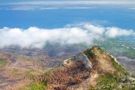 Beautiful landscape in Crimea, view from top of Ai-Petri mountain, forest valley and white clouds in sky