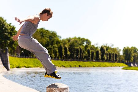 Young man in sportswear jumping and practicing parkour outside on stone fence over river embankment on clear summer day with blue sky at background. Active lifestyle and extreme sports concept