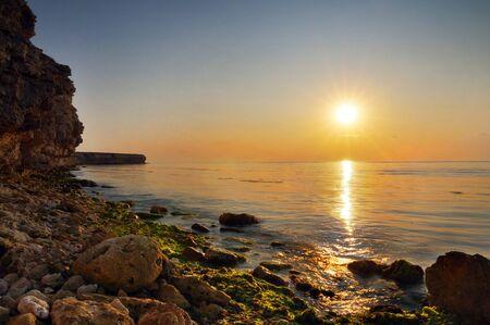Beautiful golden sunset over Black sea rocky coastline in Crimea on summer day. Natural landscape background and wallpaper