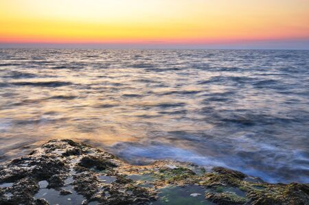 Beautiful pink sunset and water stones with green moss over Black sea rocky coastline in Crimea on summer day. Natural landscape background and wallpaper Banque d'images