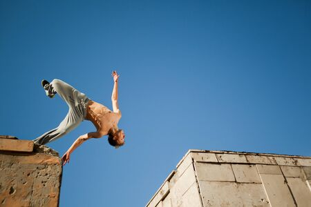 Young man jumping and practicing parkour between two buildings outside on clear summer day with blue sky at background. Active lifestyle and extreme sports concept Banco de Imagens
