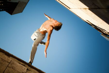 Young man jumping and practicing parkour between buildings outside on clear summer day with blue sky at background, bottom view. Active lifestyle and extreme sports concept Banco de Imagens