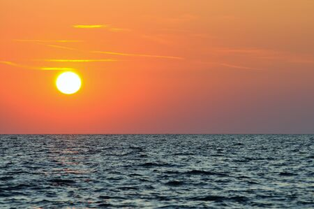Beautiful colorful sunset over wavy waters of Black sea in Crimea on summer day. Natural landscape background and wallpaper