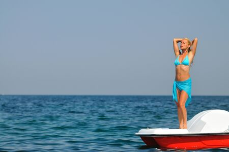 Young blond woman in blue bikini standing on white catamaran in sea and smiling on sunny summer day. Happiness, vacations and freedom concept