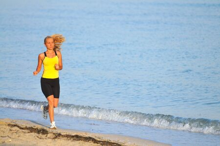 Young woman in sportswear and sneakers running near still sea edge and smiling on sunny summer day. Happiness, vacations and freedom concept