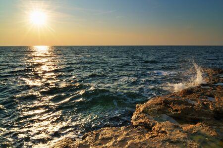 Beautiful pink sunset and water stones over Black sea rocky coastline in Crimea on summer day. Natural landscape background and wallpaper