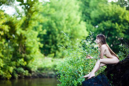 Junge schöne Frau, die am Sommertag auf Baumstamm über Wasser mit Bäumen und grünem Gras im Hintergrund sitzt. Schönheit des Körper- und Sommerlandschaftskonzepts der Frau Standard-Bild