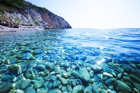 Seascape of still blue sea waters shore, stone beach and green rock behind on summer clear day with sun and blue sky. Still landscapes of travels and destination scenics