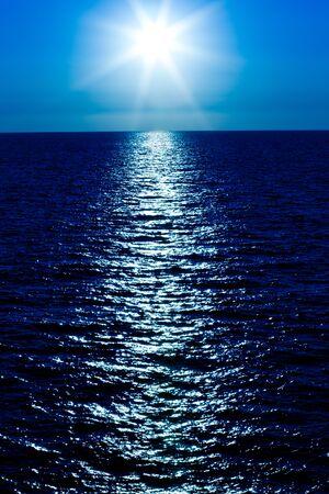 Paisaje marino de la superficie del mar inmóvil, sol dorado en el cielo en un día claro de verano. Paisajes inmóviles de viajes y paisajes de destino.