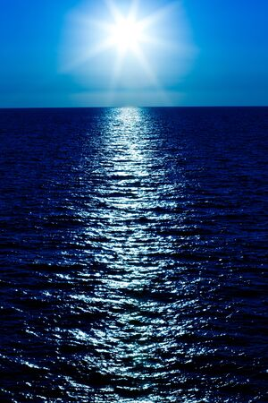 Seascape of still sea surface, golden sun in sky on summer clear day. Still landscapes of travels and destination scenics