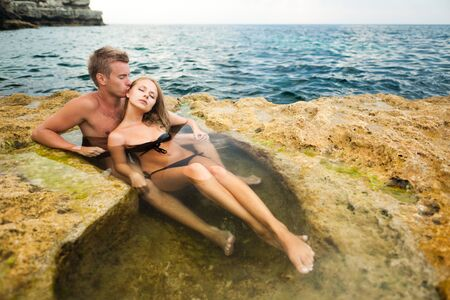 Young happy beautiful couple woman and man enjoying time in natural rock pool with water with rocks wall at background on clear summer day. Travelling, vacations, romantic weekend, honeymoon concept 免版税图像