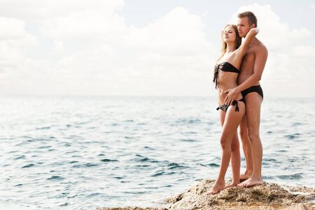 Young happy beautiful couple woman and man standing on rocks and looking at each other with sea at background on clear summer day. Travelling, vacations, romantic weekend, honeymoon concept
